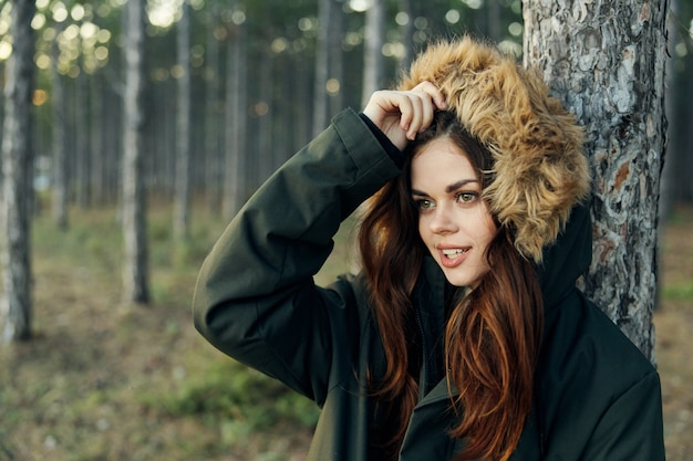 Woman in a jacket with a hood near a tree on nature lifestyle in the forest.
