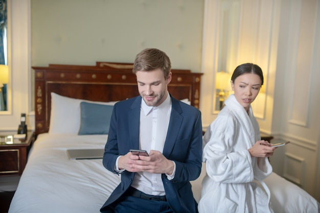 A woman jealously looking at man texting his lover