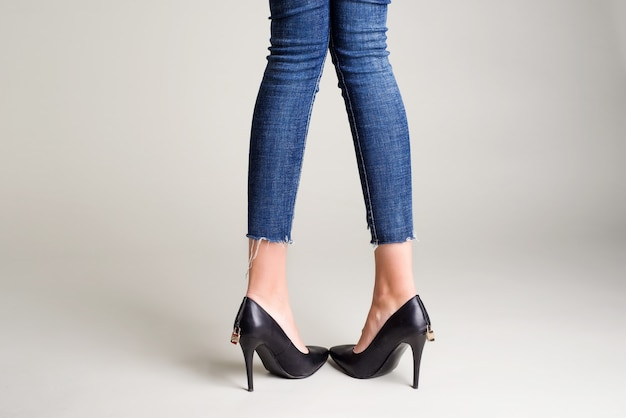 Woman in jeans black high heel shoes with a padlock posing