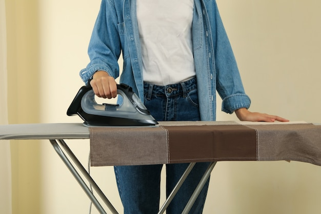 Woman in jeans ironing kitchen towel on ironing board
