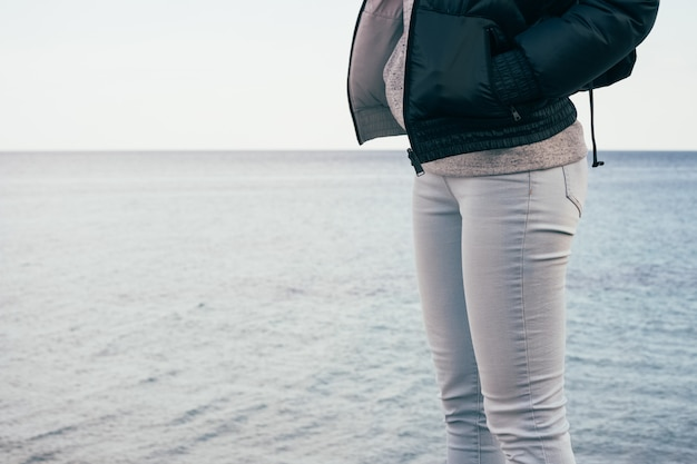 Woman in jeans and jacket standing on the sea background