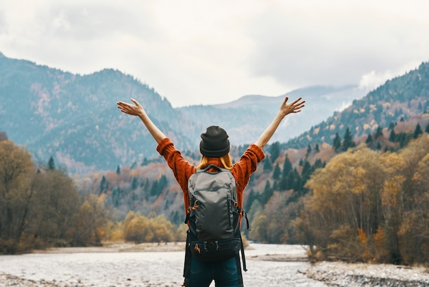 Woman in a jeans and orange sweater with a backpack in the mountains