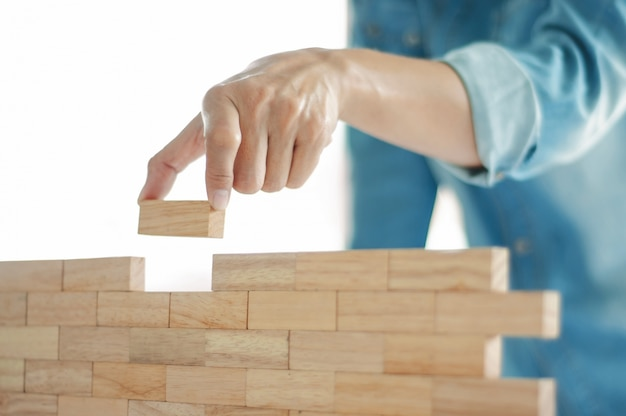 Woman in jeans shirt holding blocks wood game (jenga) building concept