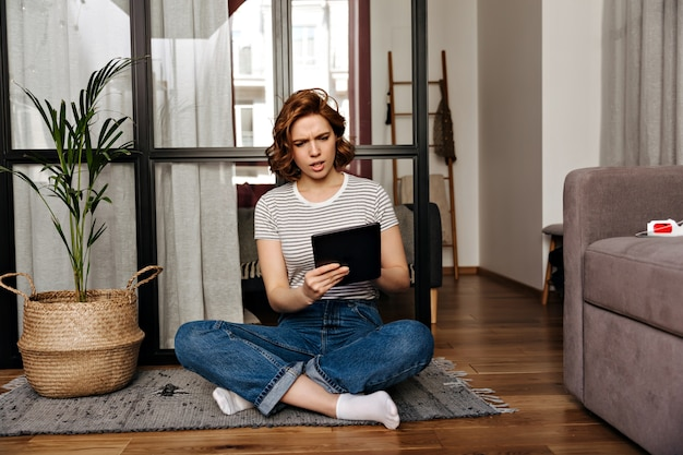 Woman in jeans sits on floor in apartment and looks at her tablet with misunderstanding.