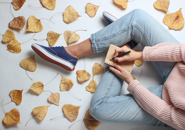 A woman in jeans and sneakers sits on white table among the fallen yellow leaves and writes in a notebook. work journalist. autumn time. working space.