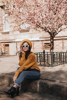 Woman in jeans and sweater is resting on curb against background of sakura. portrait of lady in stylish outfit in parisian style enjoying spring weather