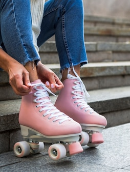 Woman in jeans tying shoelaces on roller skates