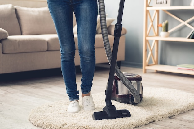 Woman in jeans using a vacuum cleaner