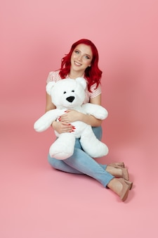 Woman in jeans with red hair hugs a large white teddy bear sitting on the floor