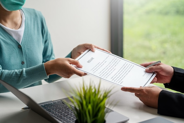 Woman job applicant submit an application to an employer to read a resume at the office.