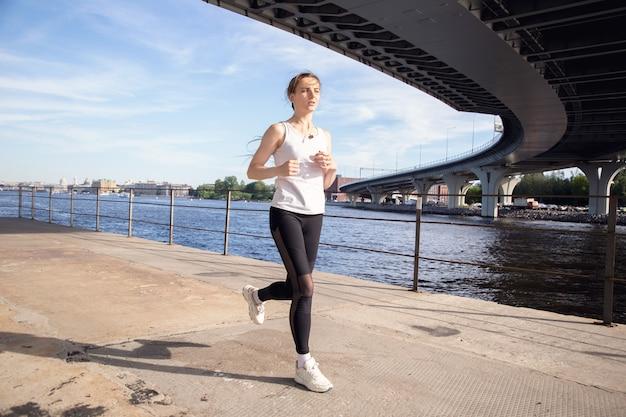 夕方に堤防に沿ってジョギングする女性