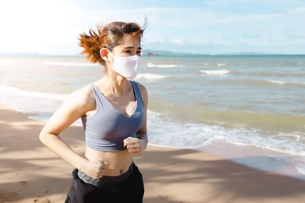 暖かい夏の朝にビーチでジョギングする女性