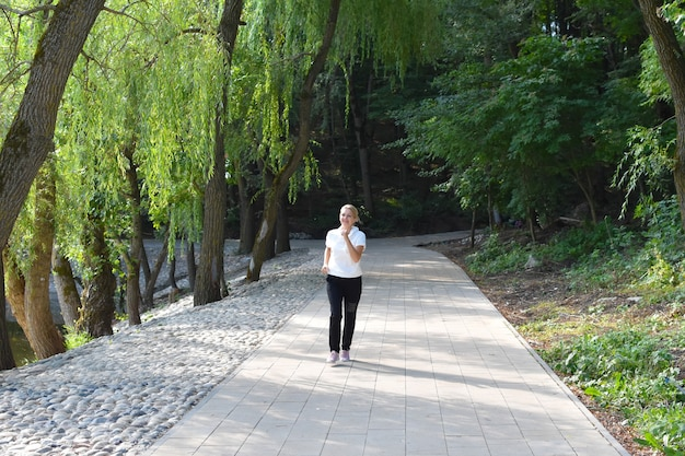 Woman jogging in city green park in summer