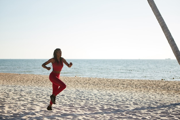 砂浜のビーチでジョギングの女性