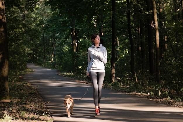 Женщина, бег с собакой в красивом лесу. молодая женщина с домашним животным делает беговые упражнения по пересеченной местности на свежем воздухе.