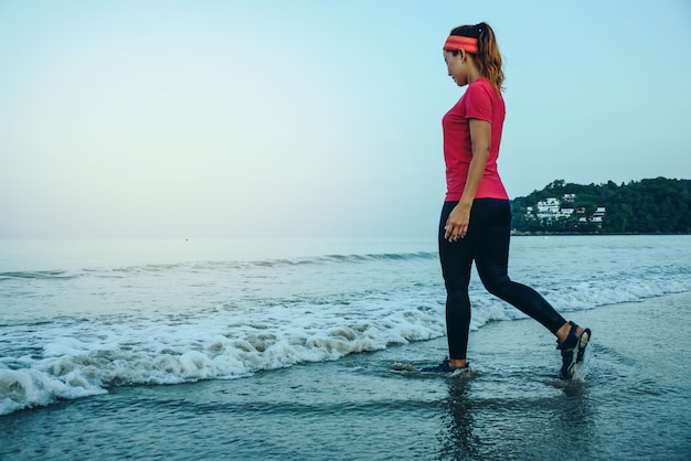 Woman jogging workout on the beach in the morning.