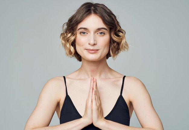 女性は灰色の背景とスポーツウェアのフィットネス瞑想で一緒に手のひらに参加しました