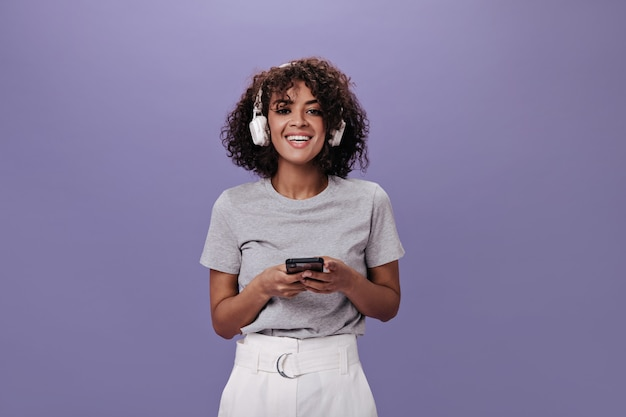 Woman in joyful mood poses in headphones and holds phone