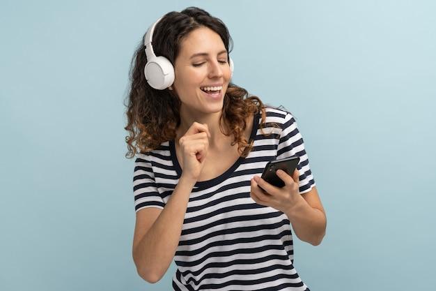 Woman joyful wearing wireless headphones listening to music, holding mobile phone in hand, dancing
