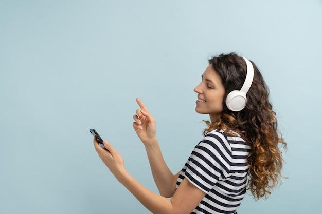 Женщина радостная носить беспроводные наушники, слушать музыку, держа в руке мобильный телефон, танцевать