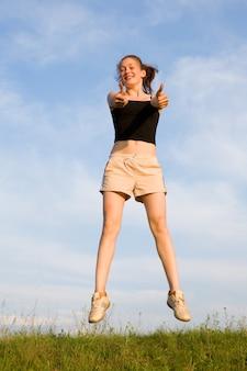 Женщина прыгает в поле под голубым небом