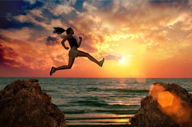 여자는 바다에 일몰에 바위에 점프