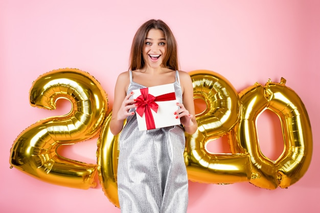 Woman jumping in the air with gift box in front of 2020 christmas balloons isolated over pink