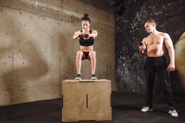 Woman jumping on fit box with male trainer