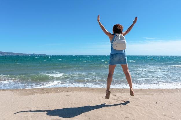 화창한 날에 해변에서 기쁨을 위해 점프하는 여자