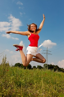 Woman jumping in front of power pole