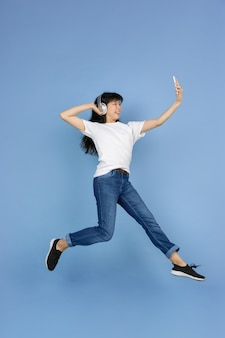 Woman jumping high and taking selfie with headphones on blue