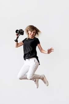 Woman jumping and holding a camera