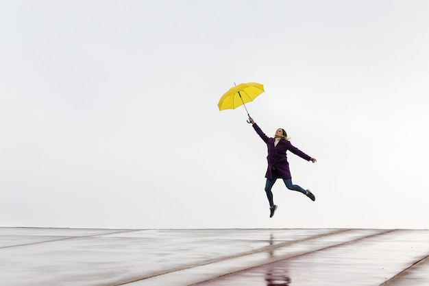 Woman jumping on the horizon with a yellow umbrella on a rainy day.