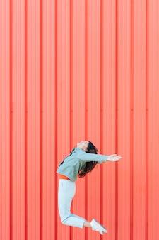 Женщина прыгает в воздухе на фоне красного металла гофрированного текстурированного