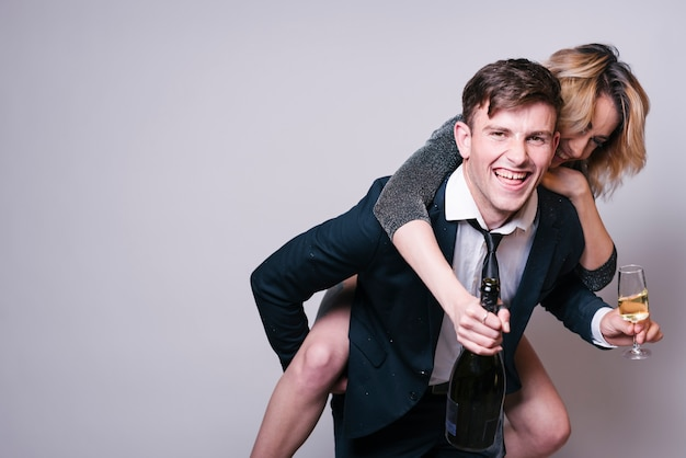 Woman jumping on man with champagne