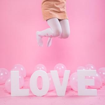 Woman jumping near love inscription
