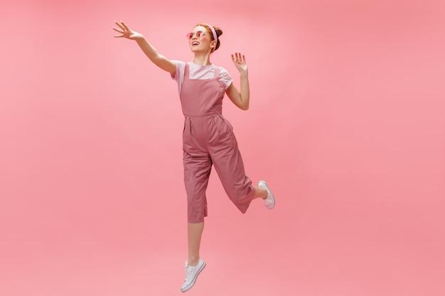 ピンクの背景にジャンプする女性。明るい服と眼鏡の赤毛の女性のフルレングスのショット。