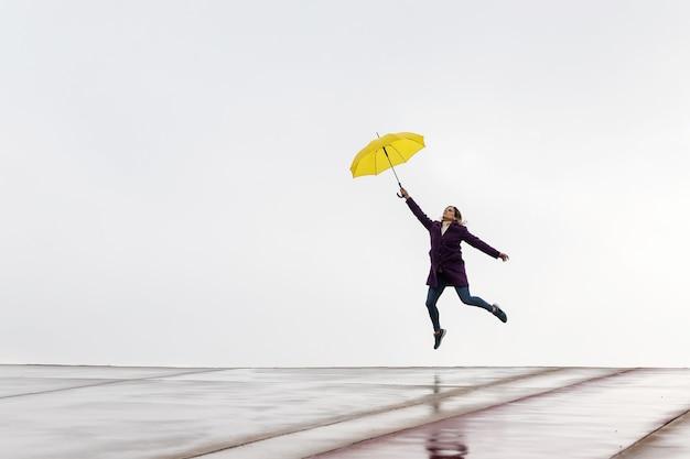 雨の日に黄色い傘を持って地平線上をジャンプする女性。