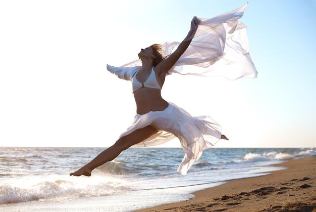 바다 해변에서 점프 하는 여자