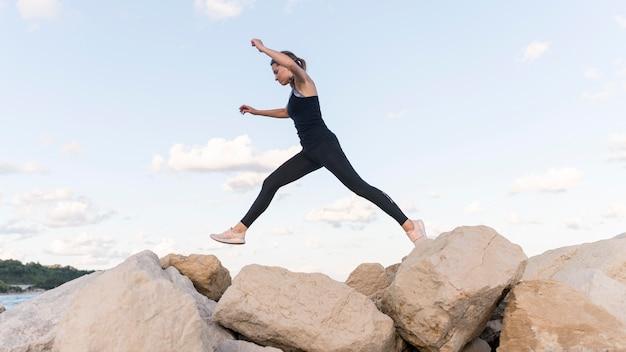 Женщина прыгает через скалы