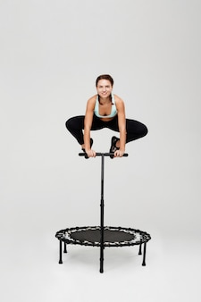 Woman jumping on rebounder with bending knees holding handle