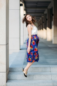 Woman jumping in the street. woman portrait outdoors in floral skirt and white top.