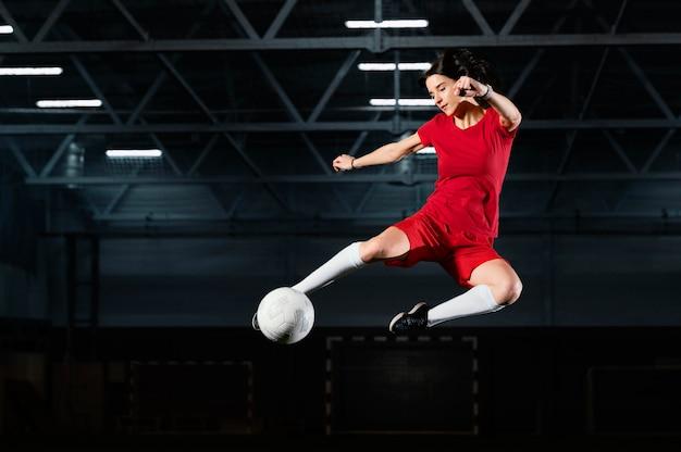 Женщина прыгает, чтобы пнуть мяч