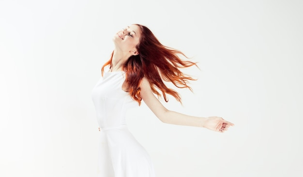 Woman jumping in white dress isolated
