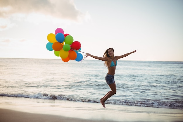 Woman jumping with balloon