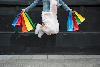 Woman jumping with colourful shopping packets