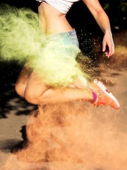 緑とオレンジ色のホリドライペイントを爆発させてジャンプする女性。女性の脚のクローズアップ