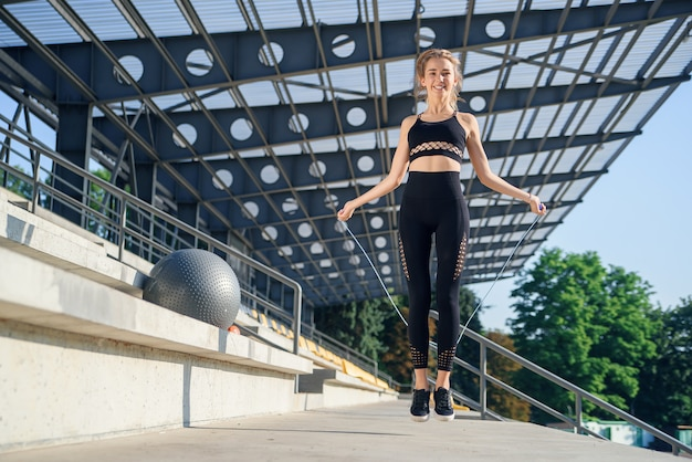 Woman jumping with skipping rope at stadium. active fitness female doing exercises outdoor. fitness concept. healthy lifestyle.