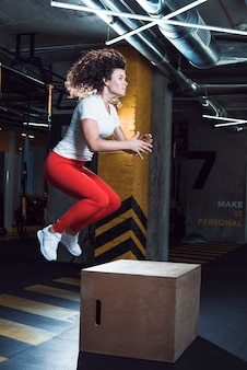 Woman jumping on wooden box in fitness club