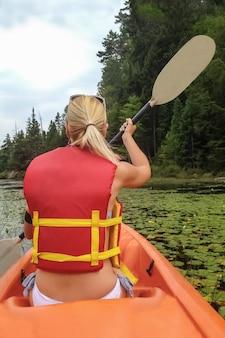 수련과 함께 호수에서 카약을 하는 여자